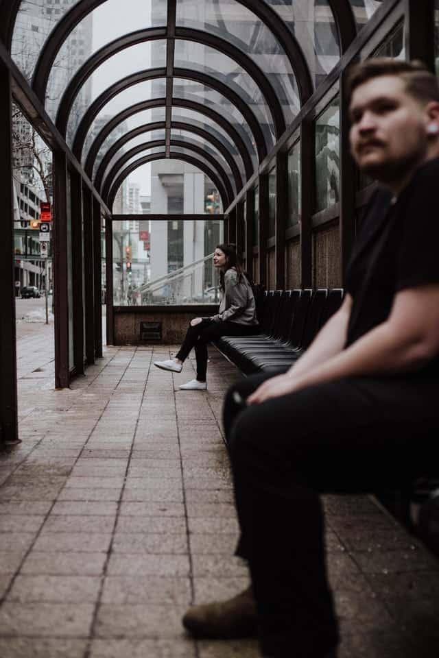בחור יושב ליד בחורה בודדה בתחנת רכבת - אילוסטרציה